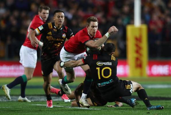 Liam Williams of the Lions is tackled by Chiefs captain Stephen Donald.