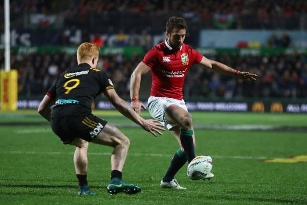 Greig Laidlaw of the Lions kicks downfield as Chiefs halfback Finlay Christie closes in.