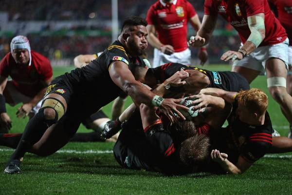 The Lions' Iain Henderson is held up over the tryline.