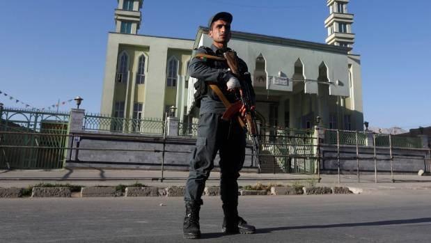 An Afghan policeman stands guard outside a mosque where a suicide bomber detonated a bomb, in Kabul on June 16.
