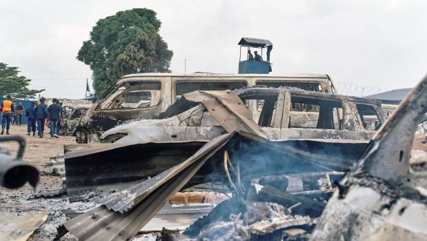 Burned vehicles seen at the front gate of the Makala prison after it was attacked by supporters of jailed Christian sect ...