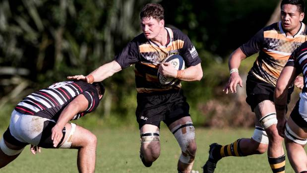 Eden Rugby's James Rutherford fends off an opponent during his side's clash with Manukau.