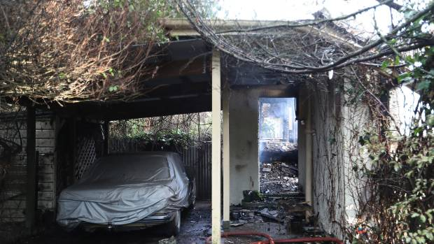 The home, densely covered in overgrowth and vegetation, was completely destroyed in the fire.