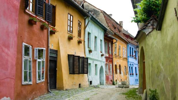 Colourful and ancient houses line a medieval street view in Sighisoara, a saxon city in Transylvania, Romania.