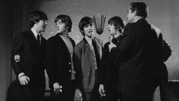 The Beatles are interviewed by a journalist during the band's tour of New Zealand in June 1964.