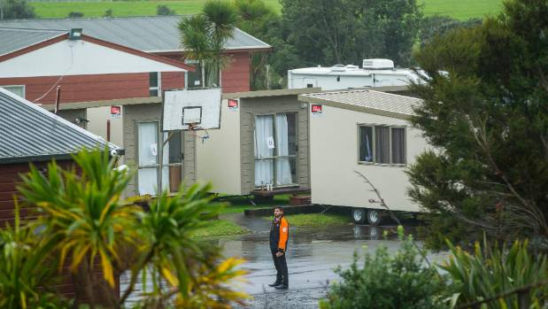 A security guard keeps media away from a section of the marae where the unpaid fellows were staying.