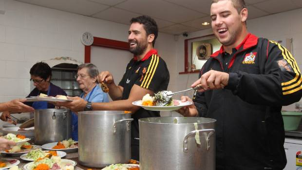 Margaret Healey, far left, is assisted by some of the Chiefs players in dishing up lunch at St. Vincent De Paul in Frankton.