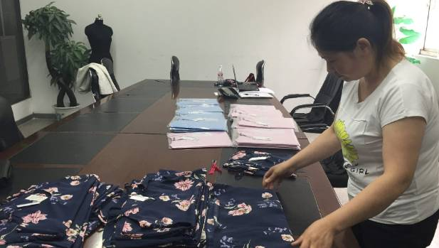A worker checks Cotton On garments at Wuxi Everbright.