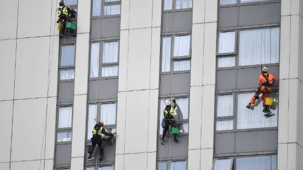 Window cleaners work on a tower block with external alumnium cladding on the Chalcots estate in Camden, UK.