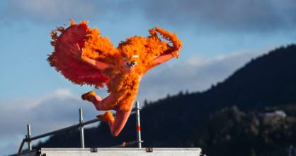 A bright orange birdman leaps from the wharf on Queenstown's lakefront.