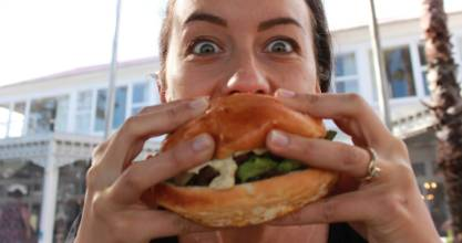 Duke of Marlborough restaurant manager Kelsey Benefield tucks into a Governor's Burger - before it's cut from the menu.