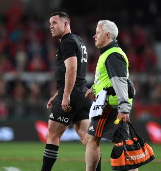 An injured Ryan Crotty leaves the pitch during the test.