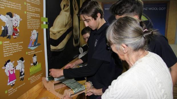 Sue Brooks, front, teaches Waitara High School student Sam Williams, 15, to use a loom.