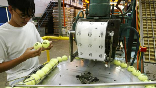 A Filipino worker inspects tennis balls at a factory in Bataan, north of Manila. The factory uses New Zealand wool to ...