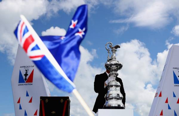 The America's Cup is brought onto the stage as a New Zealand flag is waved.