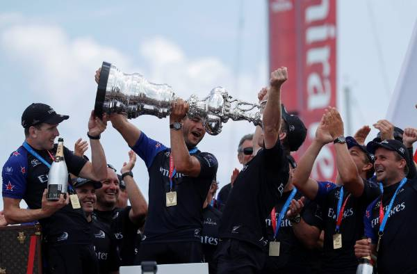 Team New Zealand's Sean Regan drinks from the America's Cup after defeating Oracle Team USA.