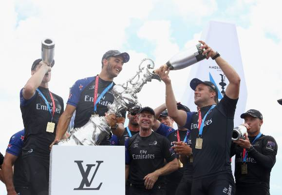the Emirates Team New Zealand fill the Auld Mug with champagne as they celebrate their win.