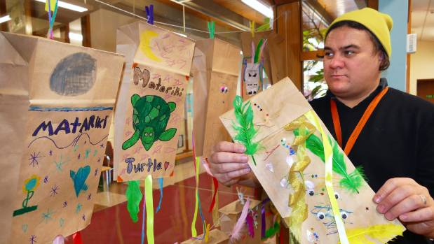 Invercargill public library community connections coordinator Jay Coote hangs kites in the windows of the children's ...