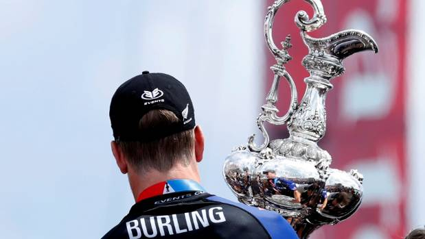 Team News Zealand helmsman Peter Burling carries off the cup after defeating Oracle Team USA.
