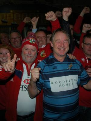 Johnsonville Rugby Football Club's Mike Segetin (centre) shows British and Irish Lions' supporters the meaning of Kiwi ...