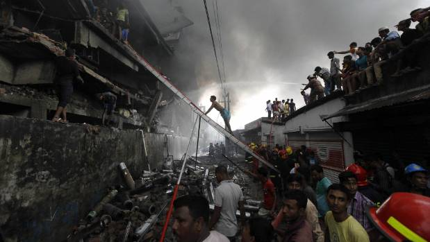 Firefighters attempt to extinguish a fire at a garment packaging factory in the Tongi industrial area on September 10, ...