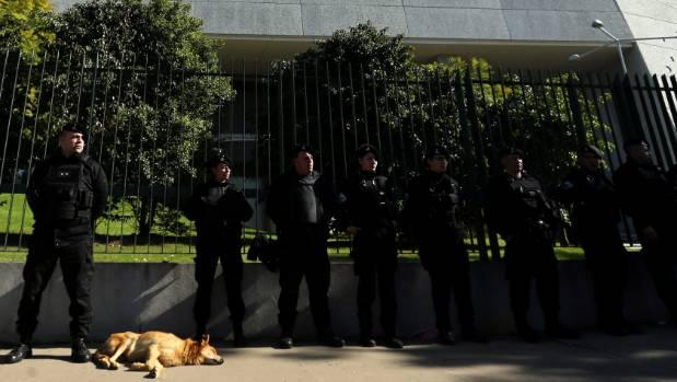 Argentine police officers stand guard as a dog lies on the sidewalk outside the hotel where the wedding of Argentina ...