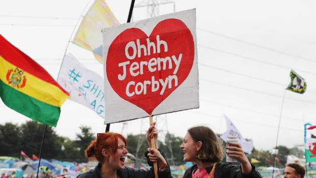 Festival-goers with a flag supporting Labour party leader Jeremy Corbyn at a guest appearance at the Glastonbury Festival.