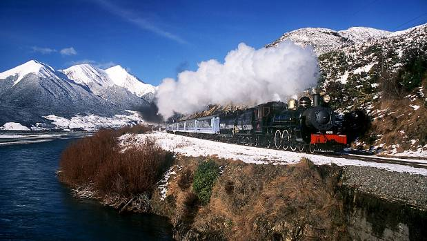 An AB 663 locomotive pulls a load of TranzScenic carriages at Mt White Bridge, near Arthur's Pass.