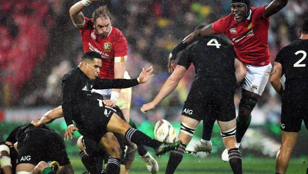 All Blacks Aaron Smith attempts a high kick as team-mate Brodie Retallick blocks out Maro Itoje.