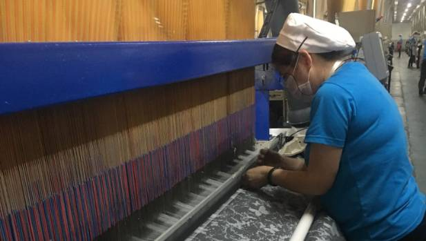 A worker checks a textile machine at Cotton On's textile supplier, the Guangyu Textile Factory.