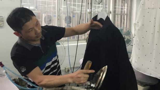 A worker steams a Cotton On shirt at Wuxi Everbright, which will be in stores in August.