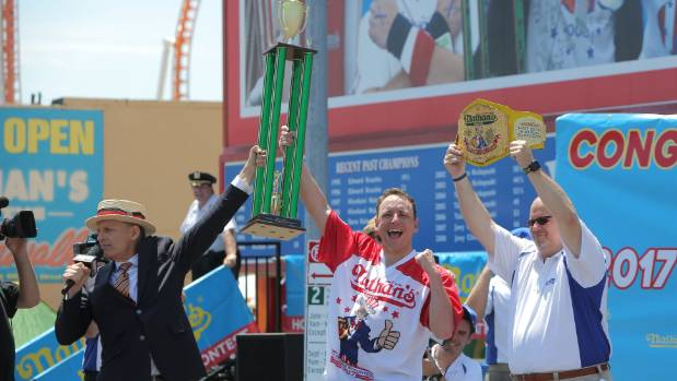 Joey Chestnut celebrates with the trophy