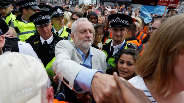 Britain's opposition Labour Party leader, Jeremy Corbyn, greets people at an anti-austerity rally in central London ...