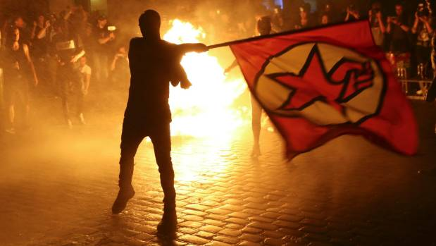 An anti-G20 protester waves a flag in front of burning garbage in Hamburg.