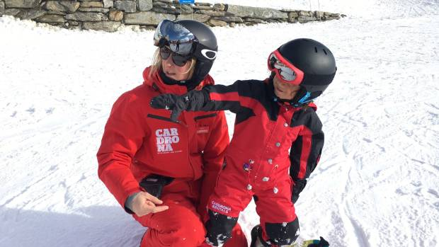 Instructor Maria Senoner teaches young snowboarder Ezrah Lodge.