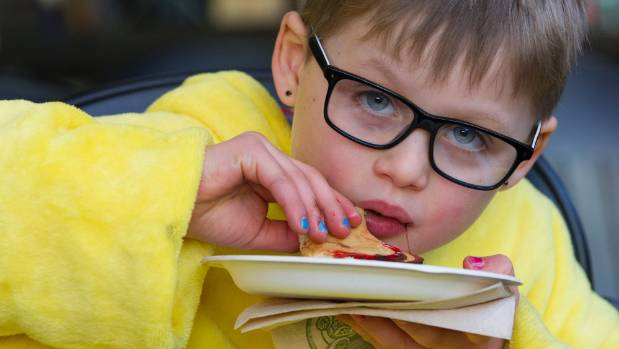Tama Marchant, 7, tucks into a pancake after reading his poem at the opening of Beyond the Page at Wellington Central ...