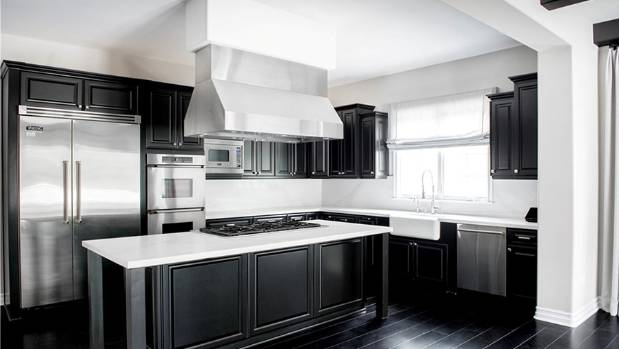 The kitchen continues the black and white theme, and includes stainless steel appliances.