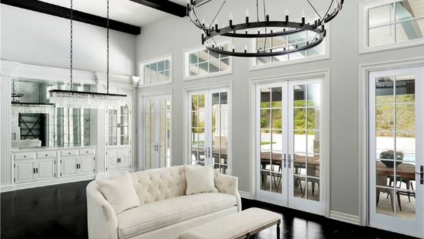 The open-plan living room room has four sets of French doors leading to an outdoor dining area.
