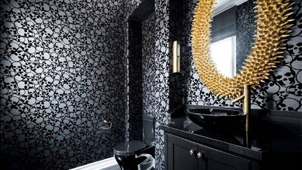 In one of the powder rooms, a flocked wallpaper by Graham & Brown features a skull pattern. Glossy black fittings and a ...