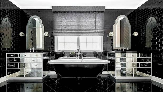 The dramatic master bathroom features dual sinks with mirrored vanities and a vintage claw-foot tub.
