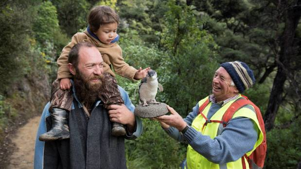 Kaipupu volunteer Gerald Harper, right, introduces visitors to a little blue penguin.