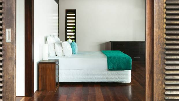 The master bedroom has Fijian vesi timber floorboards; all rooms open to the outside and have locally made vesi louvres.