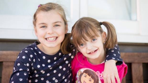 Eleven-year-old Zoe Tate, right, with sister Tess, 9, will attend the first conference in New Zealand for people with ...