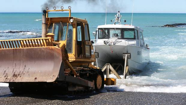 A bulldozer launches a boat from Ward Beach before seabed uplift from the earthquake compromised the launch site. (File ...