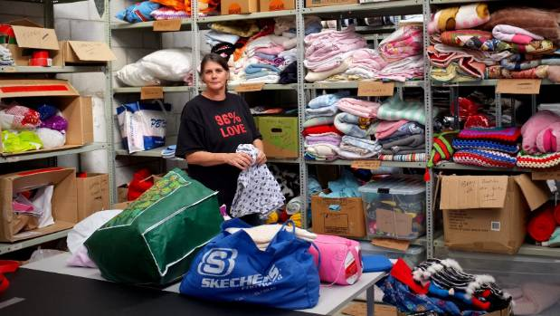 Donna Sarten surrounded by warm bedding to be donated to children in cold houses.
