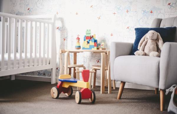 A graphic wallpaper depicting aeroplanes and engines serves as the backdrop for a young boy's room.