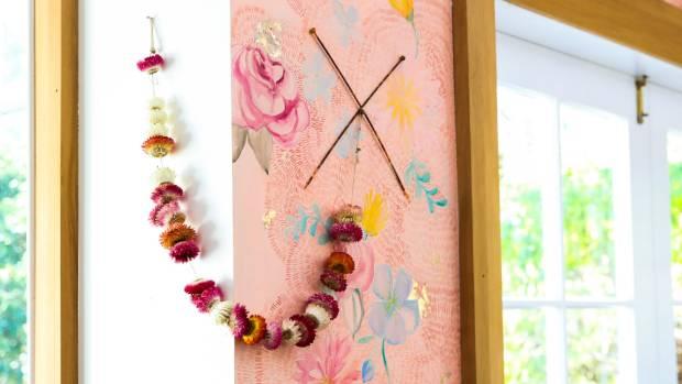 A garland of dried flowers hangs across one of Woods' original works in her studio-gallery.
