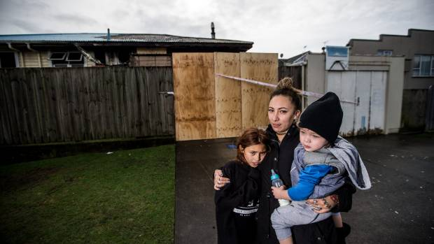 The young family outside their fire damaged home on Clawton St, New Plymouth.
