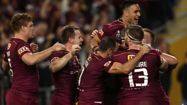 Jarrod Wallace celebrates with team-mates after scoring a try on Wednesday at Suncorp Stadium.