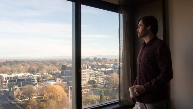 Reporter Michael Hayward looks out from an 11th floor room at the five-star Crowne Plaza Hotel in central Christchurch.